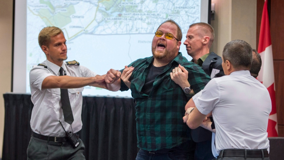 Security guards try to restrain a demonstrator from interrupting the National Energy Board public hearing into the proposed $15.7-billion Energy East pipeline project proposed by TransCanada Monday, August 29, 2016 in Montreal. (Paul Chiasson / THE CANADIAN PRESS)
