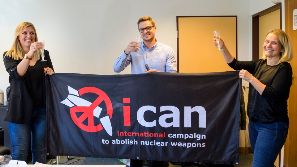 Beatrice Fihn, left, Executive Director of the International Campaign to Abolish Nuclear Weapons (ICAN), Daniel Hogsta, center, coordinator nd Grethe Ostern, right, member of the steering committee, celebrate with champagne at the headquarters of the International Campaign to Abolish Nuclear Weapons (ICAN), in Geneva, Switzerland, on Friday, Oct. 6, 2017. (Martial Trezzini/Keystone via AP)