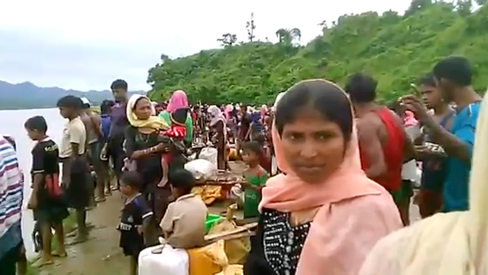 In this Oct. 5, 2017, video released by Arakan Rohingya National Organization, villagers are seen preparing to cross a river towards the Maungdaw township in the Rakhine state that borders Bangladesh. (Arakan Rohingya National Organization via the AP)