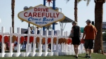 People walk by crosses placed near Las Vegas' famous sign on Thursday, Oct. 5. (AP Photo/Gregory Bull)