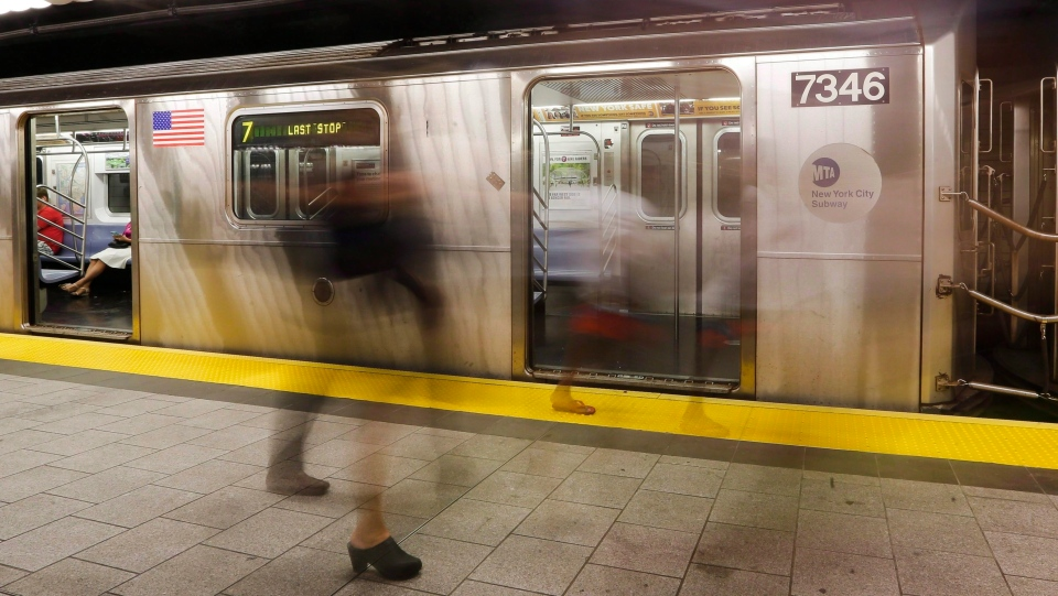 People walk on a subway platform in New York on June 22, 2016. (THE CANADIAN PRESS / AP, Frank Franklin II)