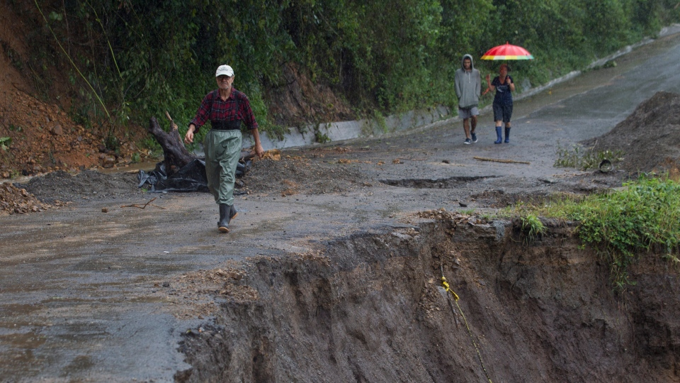 Neighbors walk under the rain past a washed out road in Alajuelita on the outskirts of San Jose, Costa Rica, Thursday, Oct. 5, 2017. (Moises Castillo/AP)