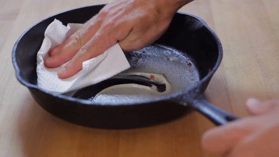 "A man wipes grease from a skillet in this still image from Metro Vancouver's ""Wipe It, Green Bin It"" campaign."