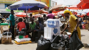People sit at a central market, in Accra, Ghana, Saturday, June 6, 2015. (AP Photo/Sunday Alamba)