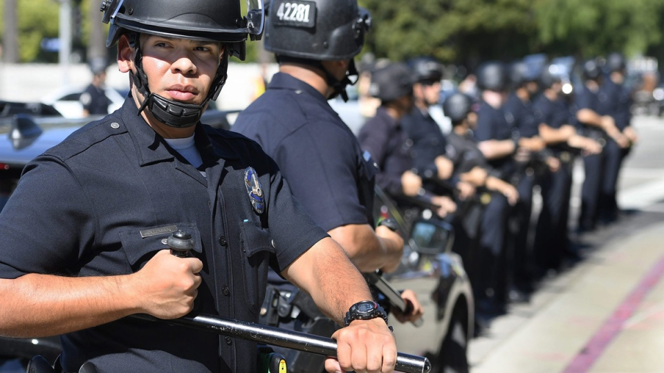 Police officers outfitted in riot gear with batons at the ready keep protesters on the sidewalk on Wilshire Boulevard, outside the Federal Building in Westwood, Calif., on Oct. 5, 2017. (John McCoy/Los Angeles Daily News via AP)