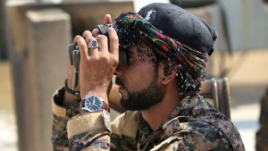 In this July 22, 2017 file photo, Abdullah, an Arab fighter with U.S.-backed Syrian Democratic Forces (SDF), looks through his binocular to an airstrike that hit an Islamic state militant group position, in Raqqa, northeast Syria. (AP Photo/Hussein Malla, File)