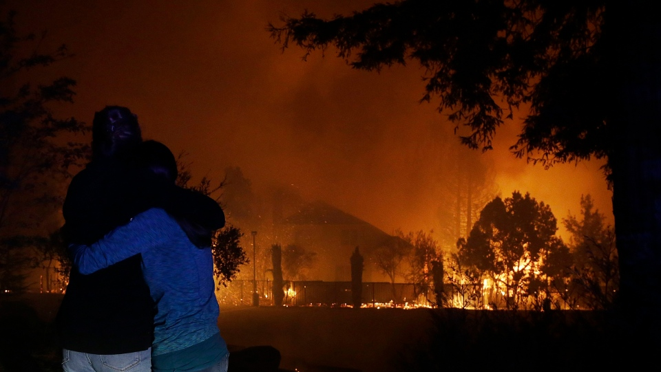 Two women hug as they watch houses burn in Santa Rosa, Calif., Monday, Oct. 9, 2017. (Jeff Chiu/AP Photo)