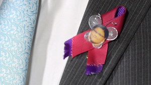 NDP MP Charlie Angus wears a pin honouring Sheridan Hookimaw, 13, who died by suicide on the Attawapiskat First Nation, as he speaks in the foyer of the House of Commons on Parliament Hill in Ottawa on Tuesday, May 10, 2016. (THE CANADIAN PRESS/Adrian Wyld)