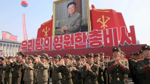 """Soldiers applaud during an event marking the 20th anniversary of the election of former North Korean leader Kim Jong Il, in portrait, as general secretary of the Workers' Party, which is the founding and ruling party of North Korea, at Kim Il Sung Square in Pyongyang, Sunday, Oct. 8, 2017. Words beneath portrait say: """"Eternal General Secretary of Our Party."""" (AP Photo/Jon Chol Jin)"""