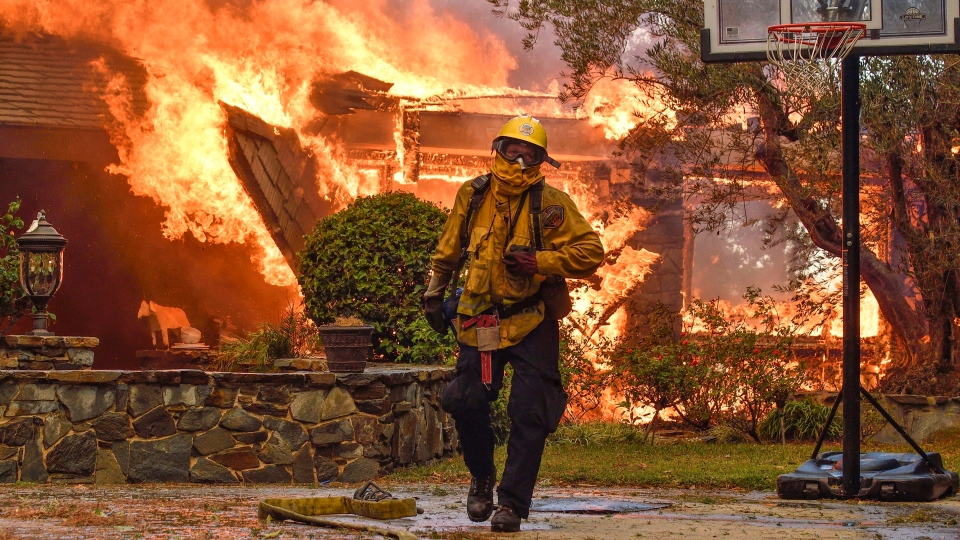 Firefighters work to extinguish a fire at a home as they battle a wildfire in Anaheim Hills, Calif., Monday, Oct. 9, 2017. (Jeff Gritchen / The Orange County Register via AP)