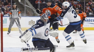Winnipeg Jets goalie Connor Hellebuyck (37) makes the save as Edmonton Oilers' Iiro Pakarinen (26) and Tucker Poolman (3) battle in front during second period NHL action in Edmonton, Alta., on Monday, October 9, 2017. THE CANADIAN PRESS/Jason Franson