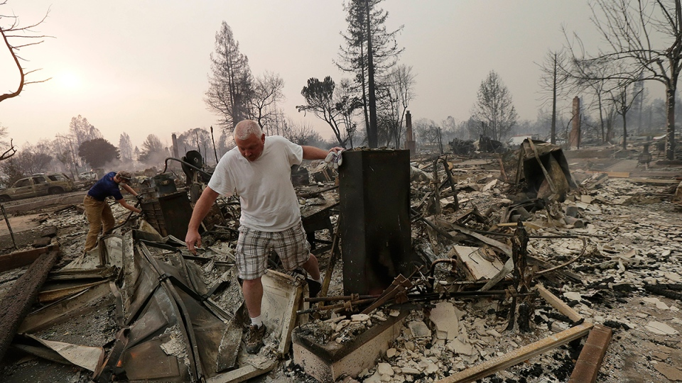 Mark Pedersen and his son Ben, left, look through the remains of their home destroyed by fires in Santa Rosa, Calif., Monday, Oct. 9, 2017. (AP / Jeff Chiu)