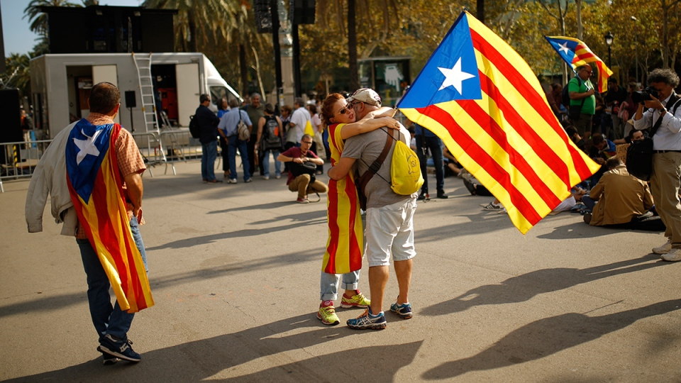A woman holds a Catalan flag as she hugs a man during a rally in Barcelona, Spain, Tuesday, Oct. 10, 2017. (AP / Francisco Seco)