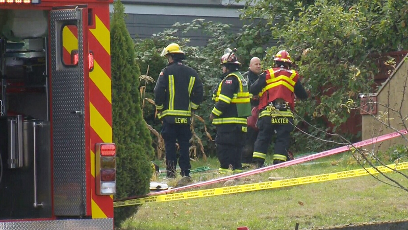 Emergency officials are seen outside a home in Nanaimo where three bodies were found on Tuesday, Oct. 10, 2017.