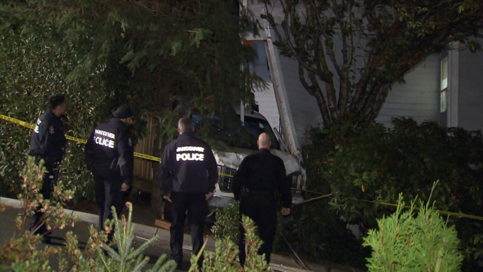 Police respond after a pickup truck with Alberta licence plates crashed through the wall of a Vancouver home. Oct. 10, 2017.