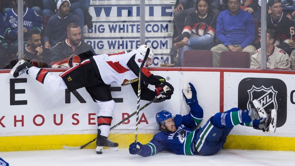 Ottawa Senators' Nate Thompson, left, checks Vancouver Canucks' Michael Del Zotto during third period NHL hockey action in Vancouver on Tuesday, October 10, 2017. (Darryl Dyck/THE CANADIAN PRESS)