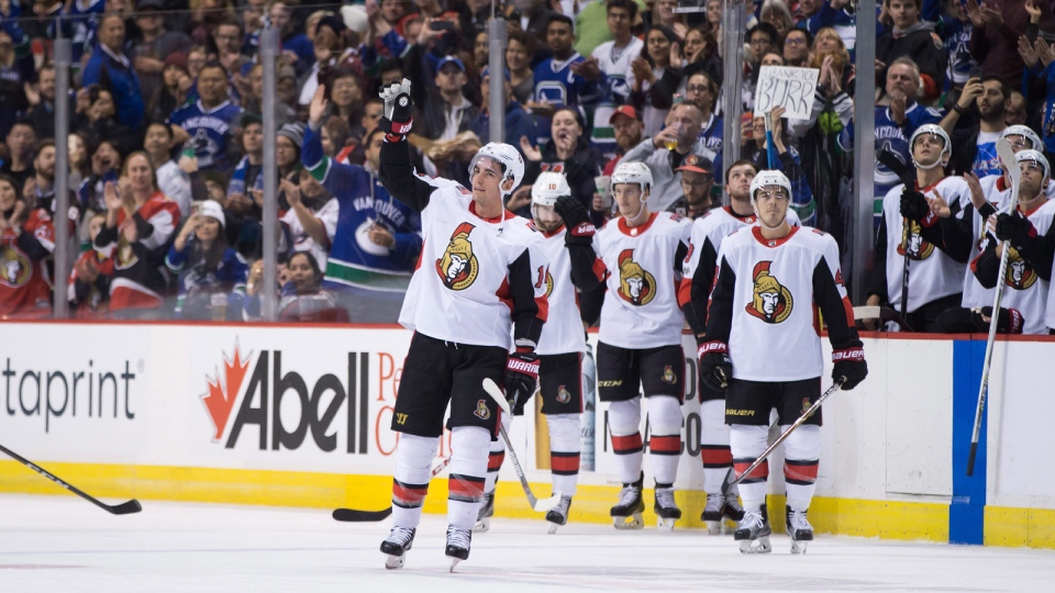 Ottawa Senators' Alex Burrows, front, acknowledges a standing ovation from the crowd after a video tribute was played for him by his former team, the Vancouver Canucks, during first period NHL hockey action in Vancouver on Tuesday, October 10, 2017. (Darryl Dyck/THE CANADIAN PRESS)