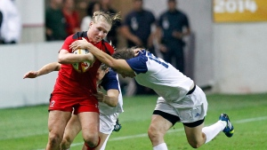 Canada's Mandy Marchak, left is grabbed by two French players as she runs with the ball, during the semi final match of the Women's Rugby World Cup 2014 between France and Canada, at the Jean Bouin stadium, in Paris, Aug. 13, 2014. (AP / Remy de la Mauviniere)
