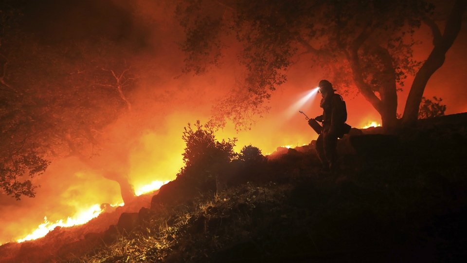 A San Diego Cal Fire firefighter monitors a flare up on the head of a wildfire, off of High Road above the Sonoma Valley in Sonoma, Calif. on Wednesday Oct. 11, 2017. (Kent Porter / The Press Democrat)