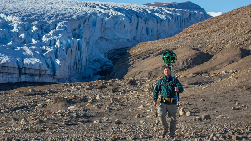 A Parks Canada staff member hikes near Air Force Glacier with the Google Trekker, Quttinirpaaq National Park. (Parks Canada / Ryan Bray)
