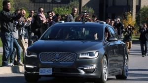 People watch as an autonomous car drives down an Ottawa street as the City of Ottawa and Blackberry QNX demonstrate the vehicle, Thursday, October 12, 2017, in Ottawa. (THE CANADIAN PRESS/Fred Chartrand)