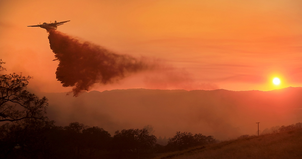 A Cal Fire air taker makes a drop on a wildfire at sunset as the pilot protects structures on the Hawkeye Ranch above Geyserville, Calif., Thursday, Oct. 12, 2017. (Kent Porter / The Press Democrat)