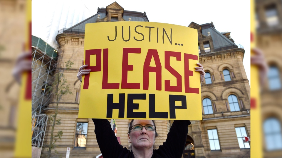 A public servant holds a sign imploring Prime Minister Justin Trudeau to resolve problems with the Phoenix pay system, during a protest outside the Office of the Prime Minister and Privy Council in Ottawa on Thursday, Oct. 12, 2017. THE CANADIAN PRESS/Justin Tang