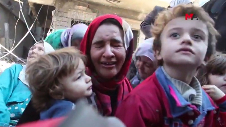 This frame grab from a video provided on Friday, Oct. 13, 2017 by Turkey-based Kurdish Mezopotamya agency media outlet that is consistent with independent AP reporting, shows a Syrian woman with her child cries after she fled from the areas that still controlled by the Islamic State militants, in Raqqa, Syria. (Mezopotamya Agency, via AP)