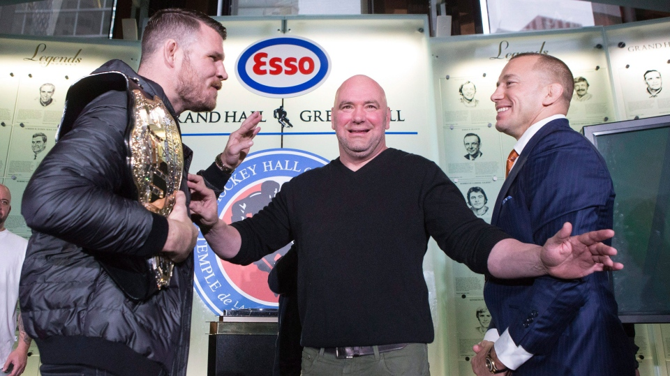 Canadian fighter Georges St-Pierre (right) and British fighter Michael Bisping 'square off' as UFC President Dana White stands between them as they promote UFC 217 during a news conference in Toronto on Friday October 13, 2017. THE CANADIAN PRESS/Chris Young