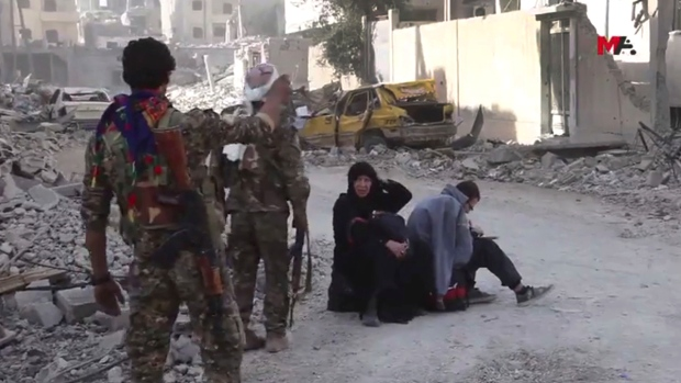 Syrian civilians with SDF fighters in Raqqa