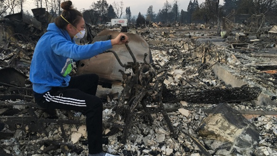Natasha Wallace sits on the remains of her scooter in the charred remains of her home in Santa Rosa, Calif., Wednesday, Oct. 11, 2017. (GoFundMe / Natasha Wallace via Storyful)