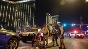 Police officers stand at the scene of a mass shooting near the Mandalay Bay resort and casino on the Las Vegas Strip, in Las Vegas, Sunday, Oct. 1, 2017. (AP / John Locher)