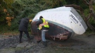 Volunteers dig out a derelict vessel on the shore of Cadboro Bay Beach in Oak Bay. Friday, Oct. 13, 2017. (CTV Vancouver Island)