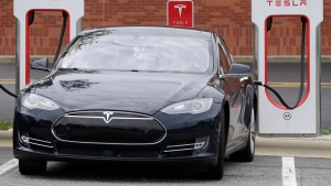 In this Saturday, June 24, 2017, file photo, a Tesla car recharges at a charging station at Cochran Commons shopping center in Charlotte, N.C. On Monday, Sept. 11, 2017. (Chuck Burton/AP)