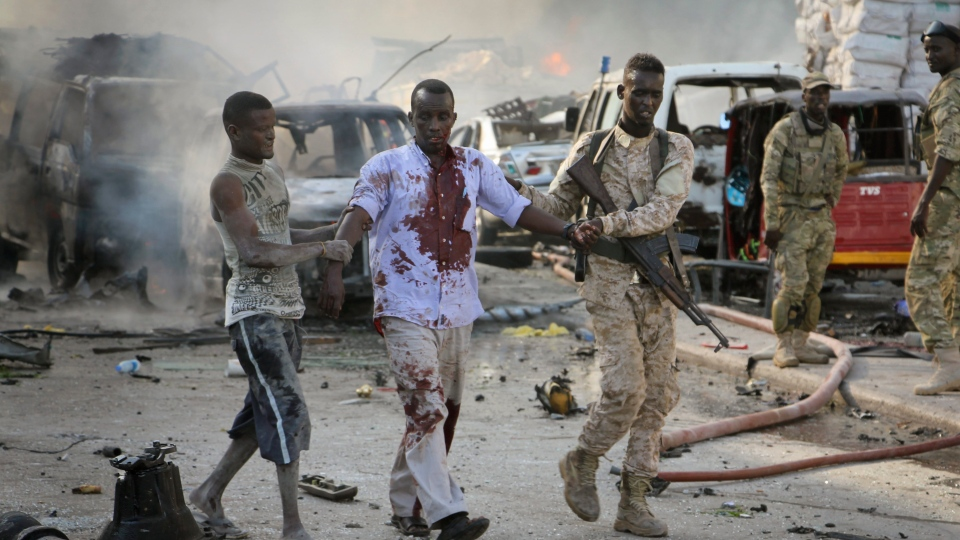 A Somali soldier helps a civilian who was wounded in a blast in the capital of Mogadishu, Somalia, Saturday, Oct. 14, 2017. (AP Photo/Farah Abdi Warsameh)