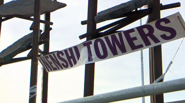 A 'Nenshi Towers' banner was removed from the Bowfort Towers public art installation in northwest Calgary late Saturday morning