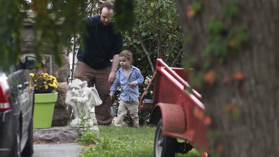 Joshua Boyle and his son Jonah play in the garden at his parents house in Smiths Falls, Ont., on Saturday, Oct. 14, 2017. (THE CANADIAN PRESS / Lars Hagberg)