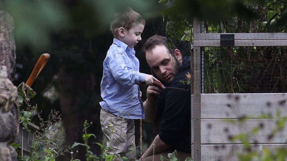 Joshua Boyle and his son Jonah play in the garden at his parents house in Smiths Falls, Ont., on Saturday, Oct. 14, 2017. THE CANADIAN PRESS/Lars Hagberg