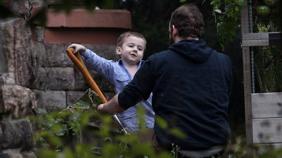 Joshua Boyle and one of his kids play in the garden at his parents house in Smiths Falls, Ont., on Saturday, Oct. 14, 2017. (THE CANADIAN PRESS / Lars Hagberg)