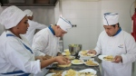 In this Tuesday, Oct. 10, 2017 photo, chefs receive instructions from Nora Hachami, left, a specialist trainer, as they prepare desserts at a restaurant in Rabat, Morocco. (AP Photo/Mosa'ab Elshamy)
