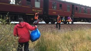 In this photo taken on Friday, Oct. 13, 2017, children run towards a train near Loch Eilt in the Scottish Highlands.  (Jon Cluett via AP)