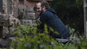 Joshua Boyle and one of his kids play in the garden at his parents house in Smiths Falls, Ont., on Saturday, Oct. 14, 2017. (THE CANADIAN PRESS/Lars Hagberg)