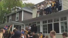 Sirens blared through Halifax's south end as some students stood on the roofs of houses and others yelled profanities at authorities. (YouTube/The Coast)