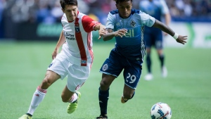 San Jose Earthquakes' Shea Salinas, left, tries to stop Vancouver Whitecaps' Yordy Reyna during the second half of an MLS soccer game in Vancouver, B.C., on Sunday, Oct. 15, 2017. (Darryl Dyck / THE CANADIAN PRESS)