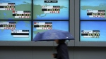 A woman walks past an electronic stock board showing Japan's Nikkei 225 index and other county's index at a securities firm in Tokyo on Monday, Oct. 16, 2017. (AP / Eugene Hoshiko)