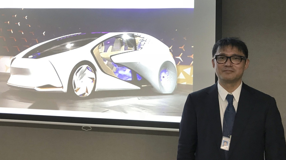 Toyota Motor Corp. manager Makoto Okabe and an image of the concept car 'TOYOTA Concept-i' series on Oct. 16, 2017 in Tokyo. (Yuri Kageyama / AP)