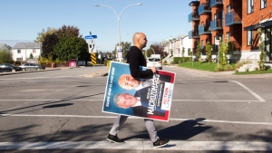 Former Canadian Olympic sprinter Nick Macrozonaris puts up campaign posters in Ste-Dorothee, Que., Friday, October 13, 2017.  THE CANADIAN PRESS/Ryan Remiorz