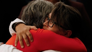 Family members comfort each other at the opening day hearings of the National Inquiry into Missing and Murdered Indigenous Women and Girls in Winnipeg, Monday, October 16, 2017. (THE CANADIAN PRESS/John Woods/Pool)