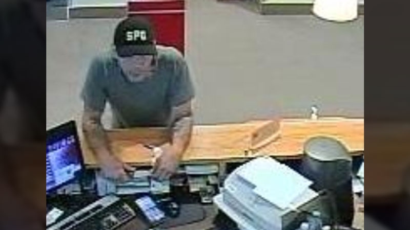 A suspect is seen holding a knife while leaning over the counter at an Abbotsford bank on Sunday, Oct. 15, 2017. (Provided)