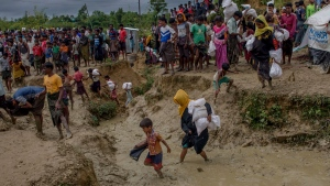 FILE - In this Sept. 28, 2017 file photo, RohingyaMuslims, who crossed over from Myanmar into Bangladesh, walk through muddy field after collecting aid from a distribution center near Balukhali refugee camp, Bangladesh. On Tuesday, Oct. 10, medical teams from the health ministry, supported by UNICEF and WHO, started a massive cholera immunization drive in the camps that accommodate the new arrivals as well as many of the hundreds of thousands of Rohingya who fled to Bangladesh during earlier spasms of violence in Myanmar, racing against time to prevent outbreaks of infectious diseases. (AP Photo/Dar Yasin, File)